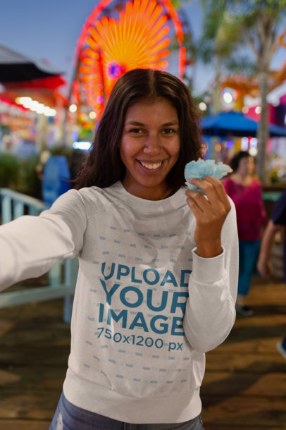 Mockup of a Woman Wearing a Sweatshirt in a Carnival Setting 18218