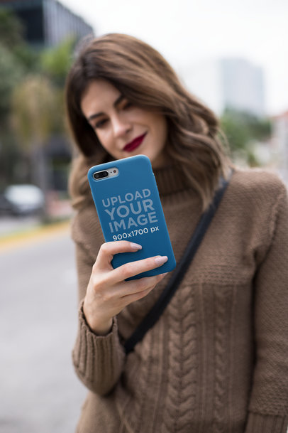 Mockup of an iPhone Case Held by a Pretty Woman Wearing a Sweater 22912