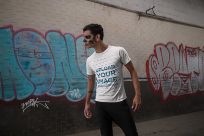 Tshirt Mockup of a Man with Spooky Makeup Against a Wall with Graffiti 23027