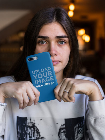 Mockup of a Woman with Blue Eyes Holding a Phone Case 22887
