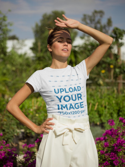 T-Shirt Mockup of a Woman in a Garden Blocking the Sun from Her Eyes 22495