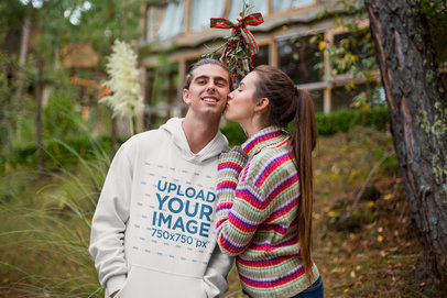 Christmas Sweatshirt Mockup of a Man Being Kissed by His Girlfriend Under Mistletoe 23515