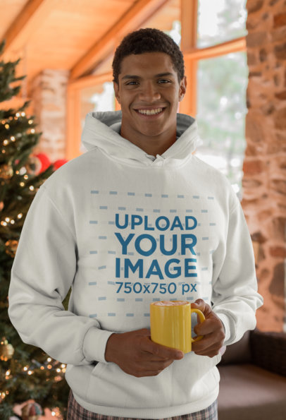 Mockup of a Man Wearing a Hoodie in Front of a Christmas Tree 23507