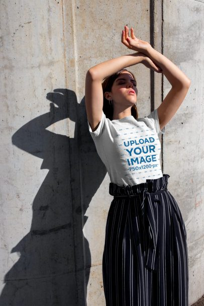 Tshirt Mockup of a Girl Blocking the Sun Leaning Against a Concrete Wall 20697
