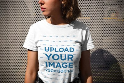 Closeup Mockup of a Woman Wearing a Round Neck Tee Looking to the Left Against Metal Fence 20689