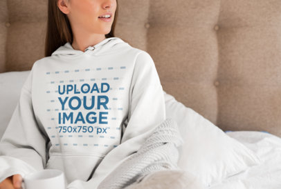 Pullover Hoodie Mockup of a Young Woman Sitting on a Bed with a Coffee Mug 23212