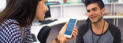 iPhone Mockup of a Young Woman Talking to a Coworker at the Office a4646