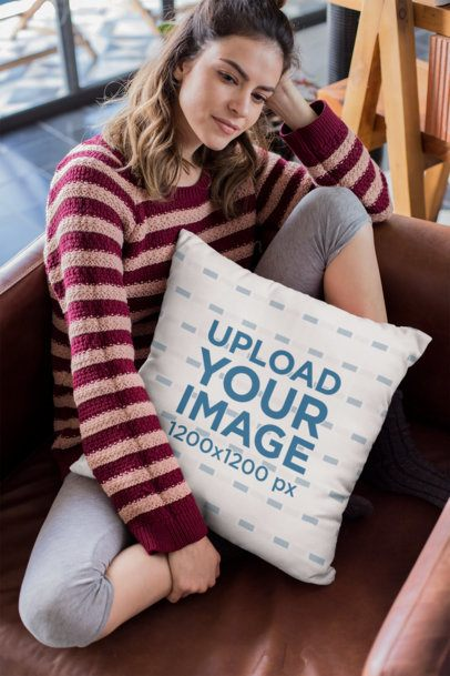 Mockup of a Girl Holding a Pillow Sitting on a Leather Sofa 23579