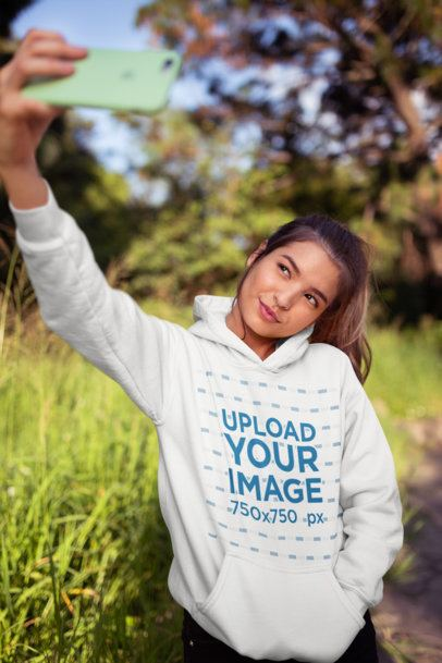 Pullover Hoodie Mockup of a Woman Taking a Selfie at the Countryside 23280