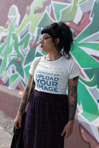 T-Shirt Mockup of a Tattooed Woman Near a Graffiti Wall 23412