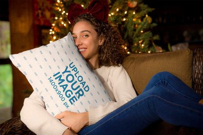 Mockup of a Woman Hugging a Pillow in Front of a Christmas Tree 23506