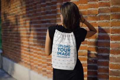Drawstring Bag Mockup Featuring a Woman Walking by a Brick Wall 23670