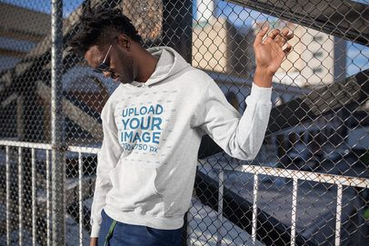 Hoodie Mockup of a Cool Young Man Leaning on a Chain-Link Fence 24313