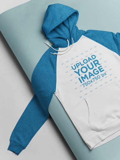 Mockup of a Raglan Hoodie Lying on a Pasteboard 24364