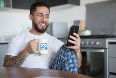 Mug Mockup of a Bearded and Tattooed Man Drinking Tea in the Kitchen 24018