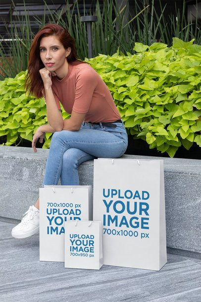 Gift Bag Mockup Featuring a Woman Sitting on a Stone Bench 24039