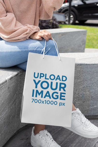 Mockup of a Gift Bag Being Held by a Girl while Sitting 24048