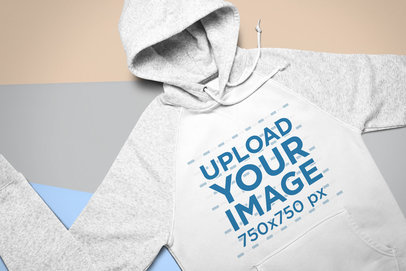 Mockup of a Heathered Raglan Hoodie Laid Flat on a Colored Surface 24542
