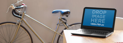 Mockup of a Laptop Sitting on Top of a Table at a Creative Office a5444