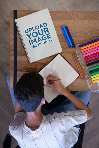 Notebook Mockup of a Boy Sketching 24127