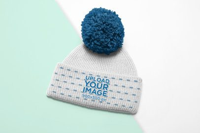 Mockup of a Beanie with a Pom Pom over a Duo Colored Surface 24559