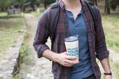 Mockup of a Man Holding a Travel Mug While Walking Outdoors 24386