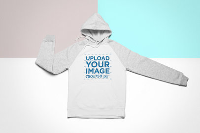 Mockup of a Raglan Hoodie Lying on a Multicolor Surface 24756