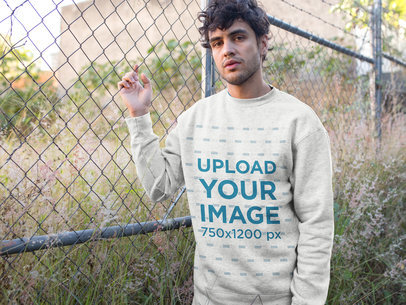 Heather Crewneck Sweater Mockup Featuring a Man Leaning Against a Fence 18182