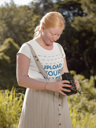 T-Shirt Mockup of a Woman Taking a  Picture with Her Vintage Camera 22001
