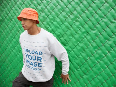 Sweatshirt Mockup of a Man Leaning Against a Green Fence 21065
