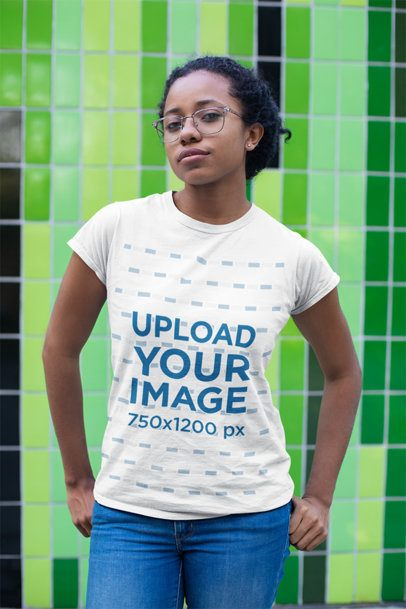 T-Shirt Mockup of a Girl with Glasses Standing in Front of a Green Mosaic 24100
