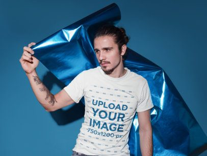 T-Shirt Mockup of a Young Man Holding a Metallic Paper Foil 18526
