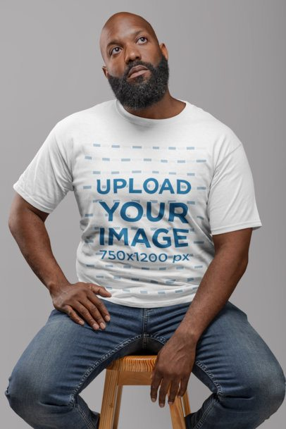 T-Shirt Mockup of a Sitting Bearded Man Looking Pensive 21527