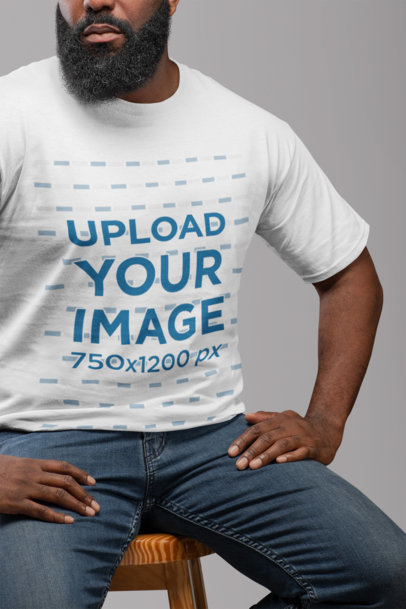 T-Shirt Mockup Featuring a Man with a Beard Sitting on a Chair 21529