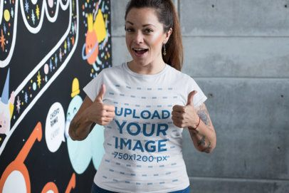 T-Shirt Mockup of a Happy Customer Giving Thumbs up Against a Graffiti Wall 26209