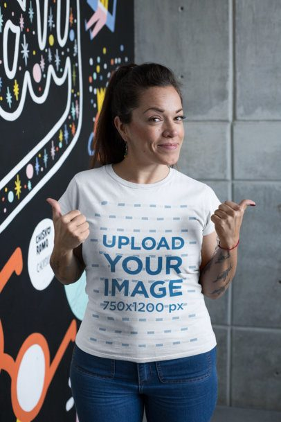 T-Shirt Mockup Featuring a Happy Customer Standing by an Art Wall 26210