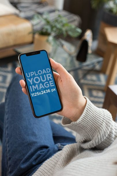 Mockup Featuring an iPhone XS Being Held by a Woman Sitting Down 25356