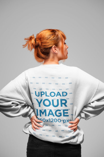 Sweatshirt Mockup of a Girl with a Red Hair Bun and Hands on Her Waist Facing Backwards 20850
