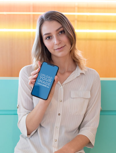 Mockup of a Cute Girl Holding Her iPhone XS Max in a Cool Illuminated Room 25433