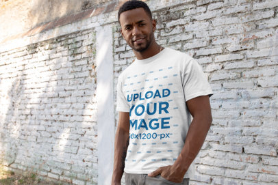 T-Shirt Mockup of a Fit Man in Front of an Old Block Wall 2592