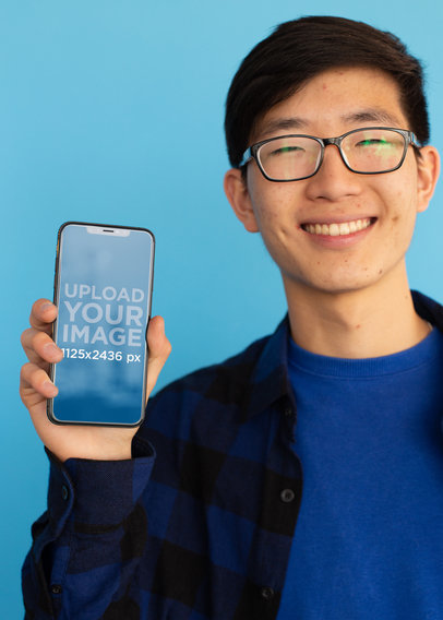 iPhone X Mockup Featuring a Smiling Man with Glasses Against a Blue Surface 25541