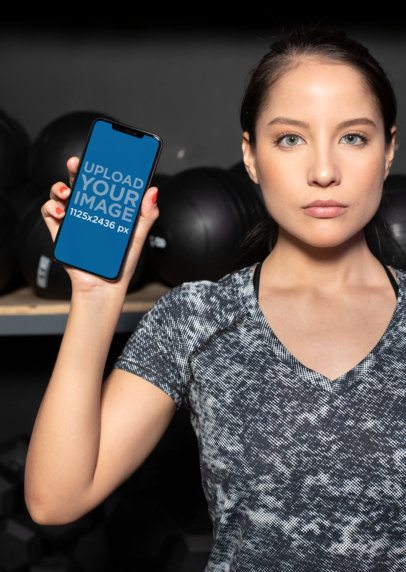 Mockup of a Girl Showing Her iPhone XS at the Gym 25981