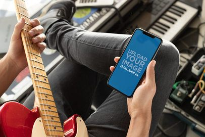 Mockup of a Man Watching His iPhone XS Max While Playing Guitar 25753