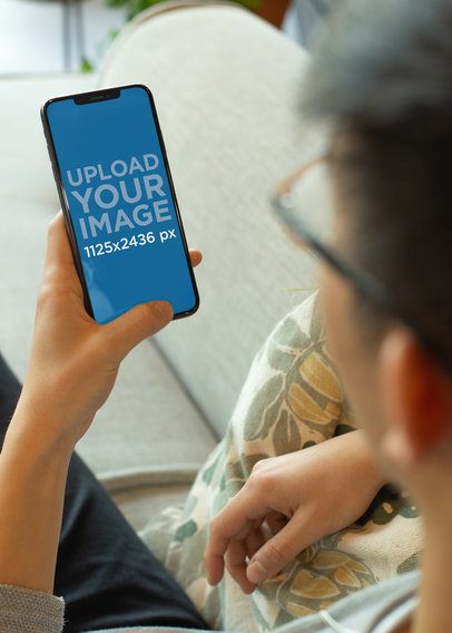 Over-The-Shoulder Mockup of a Man with Glasses Checking His iPhone XS 25534