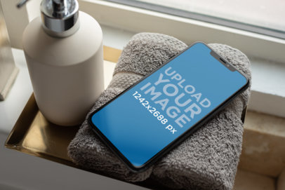 iPhone XS Max Mockup Resting over a Towel in a Bathroom 25895