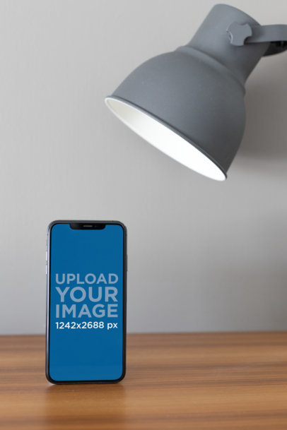 iPhone XS Max Mockup Standing Under a Desk Lamp 25896