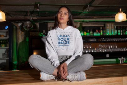 Crop Top Hoodie Mockup Featuring a Woman Sitting on Top of a Bar 26101