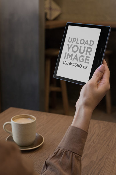 Mockup of a Woman Reading a Kindle Oasis by a Table with a Coffee Mug 26024