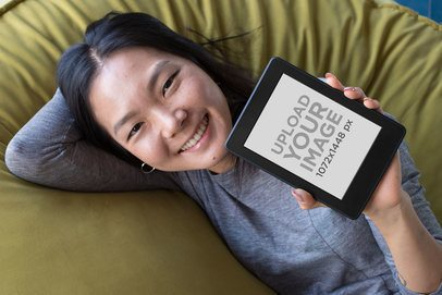 Kindle Paperwhite Mockup of a Smiling Girl Lying over a Pillow 26035