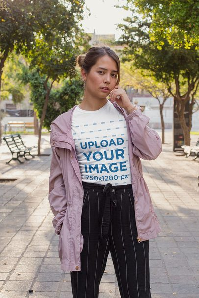 T-Shirt Mockup of a Woman in a Trenchcoat Posing at a Park 26870